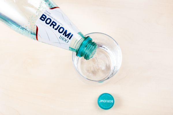 pouring borjomi water from plastic bottle