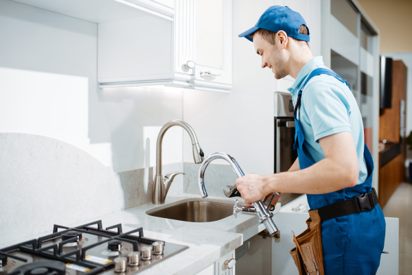 plumber in uniform changes faucet in