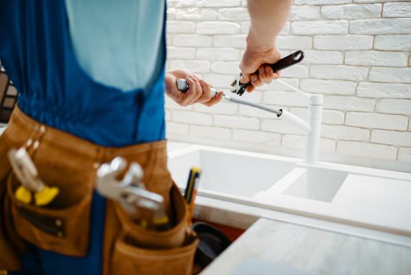 plumber in uniform fixing faucet in
