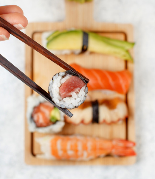 hand taking roll with chopsticks from