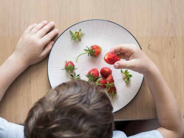 little boy eats fresh organic strawberry
