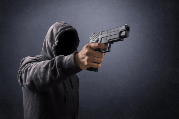 hooded man with a gun in
