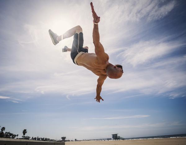 muscular man exercising on beach