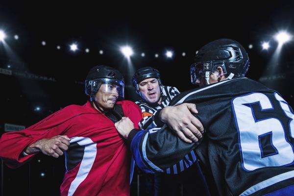 referee separating fighting hockey players