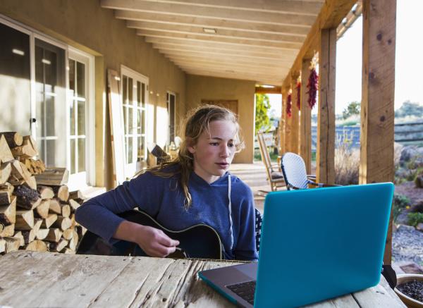 a teenage girl looking at laptop