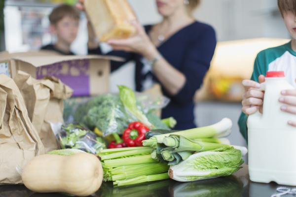 family unloading fresh produce in kitchen