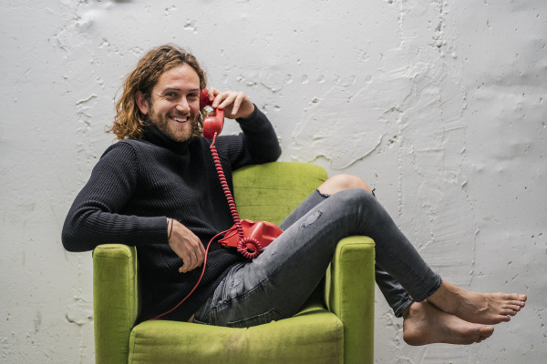 smiling man talking over telephone while
