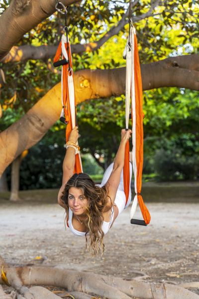 mature woman practicing aerial yoga on