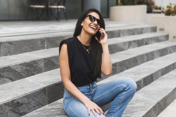 woman with sunglasses using smartphone in