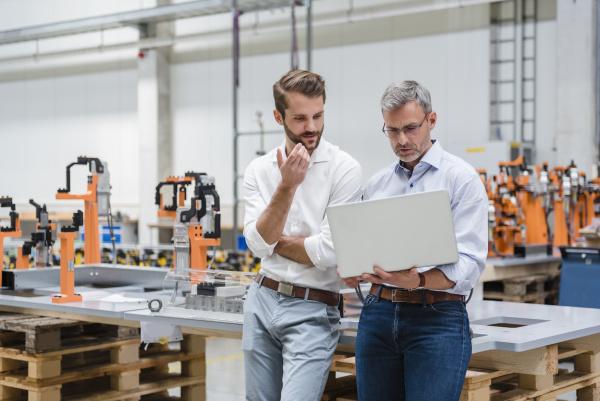 two men using laptop on factory