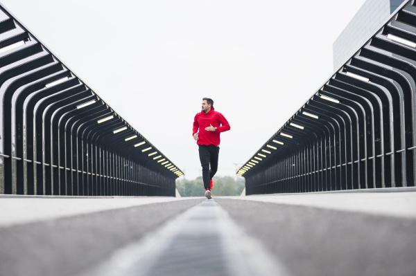 young man running on a bridge