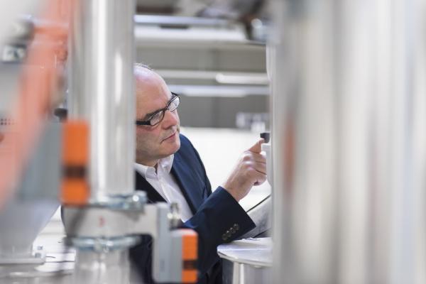 businessman examining a machine in a