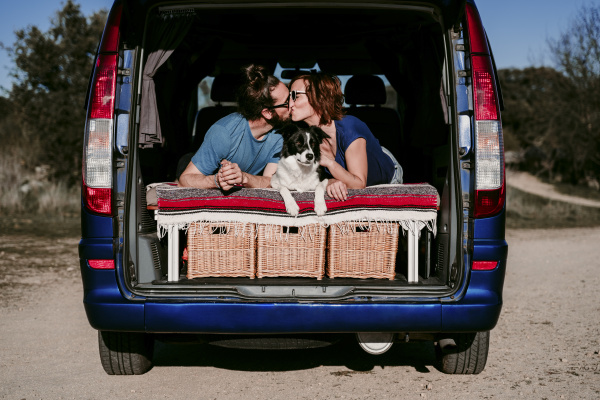 couple with dog kissing in the