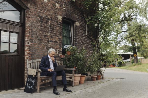 senior businessman sitting at a farmhouse