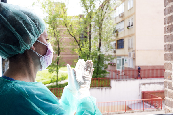 nurse clapping hands at window in
