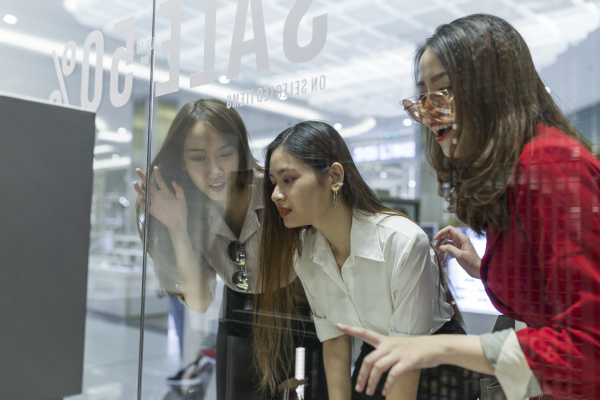 curious female friends doing window shopping