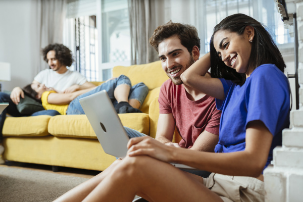 smiling young couple sharing laptop while