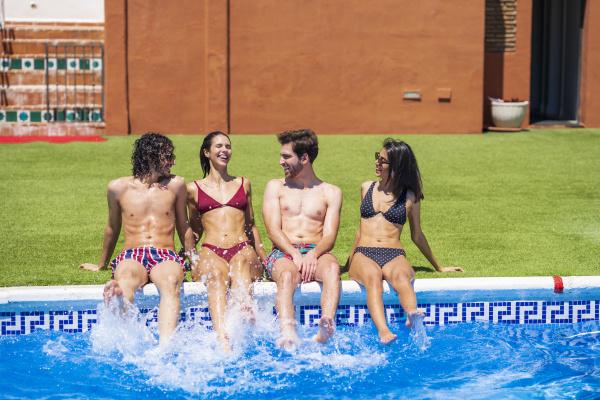 cheerful young multi ethnic friends splashing