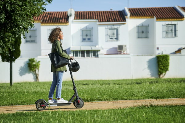 young woman riding electric push scooter