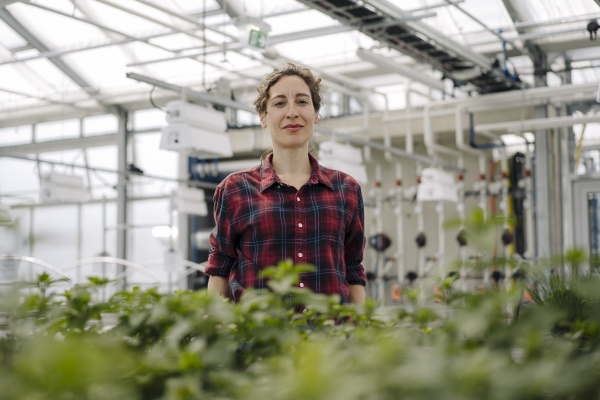 portrait of confident woman in greenhouse