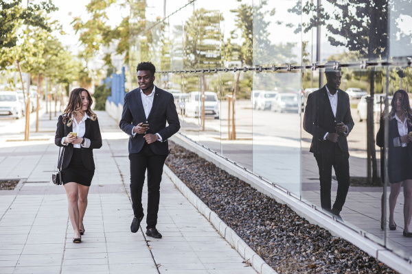 business people discussing while walking on