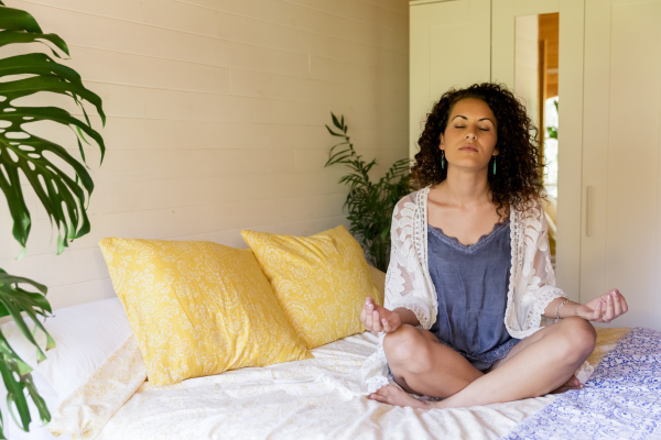 relaxed young woman meditating while sitting