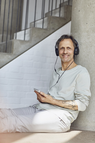 smiling senior man with headphones listening
