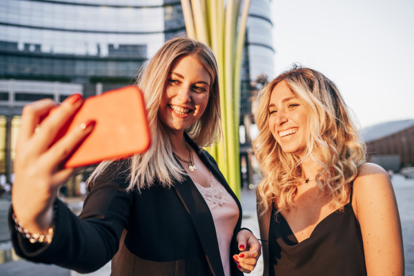 smiling businesswoman taking selfie with female