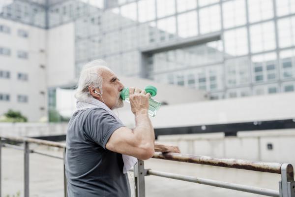 senior man drinking water while standing