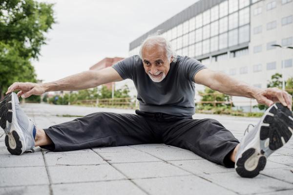 smiling senior man stretching body while