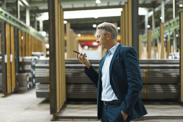 mature businessman holding mobile phone in
