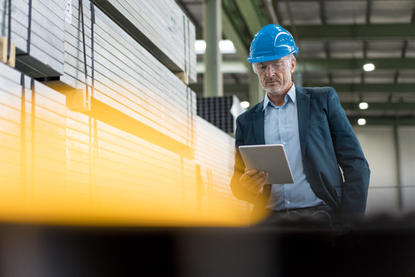 mature businessman wearing hard hat and