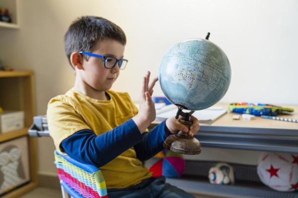 cute boy holding while touching globe