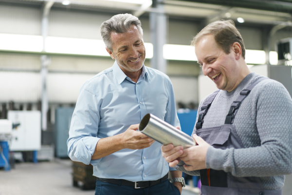 happy businessman and worker examining steel