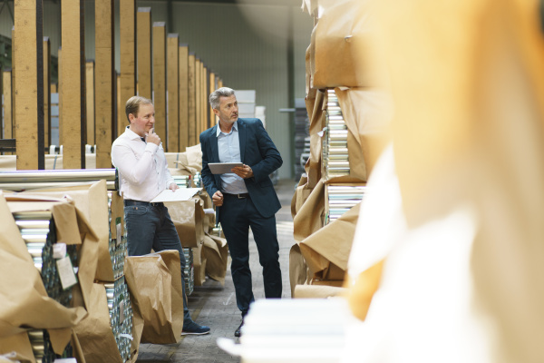 two businessmen in a factory storehouse