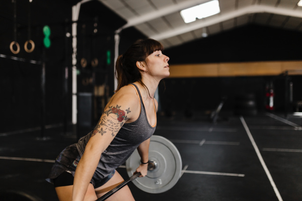 mid adult woman lifting deadlift while