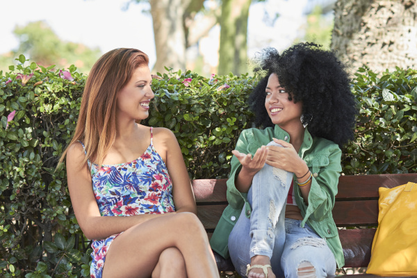 girlfriends talking and sitting on bench