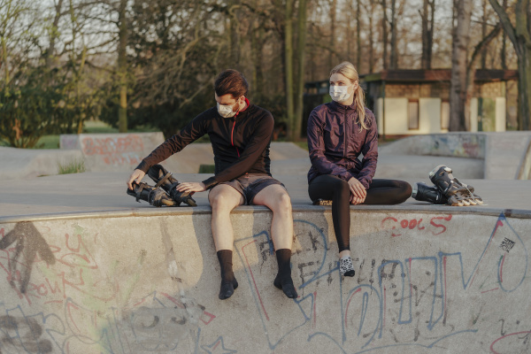young couple sitting with inline skates