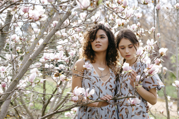 sisters looking at flowers while standing