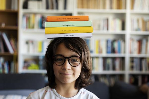 portrait of smiling boy balancing stack