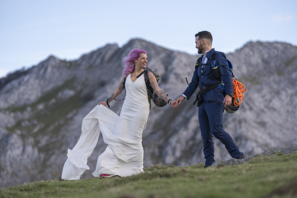 bridal couple hiking with backpacks