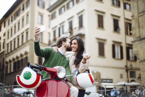 romantic man taking selfie while kissing