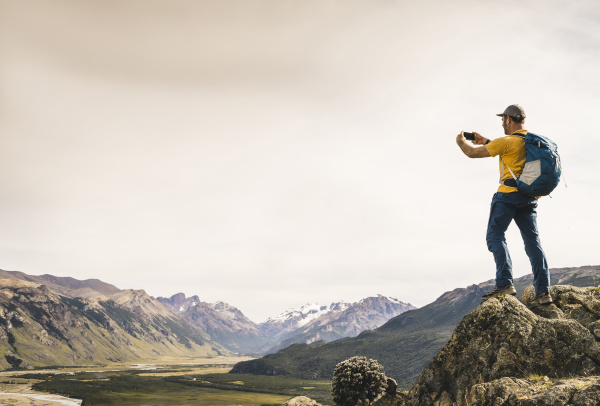 mature man photographing mountains with smart