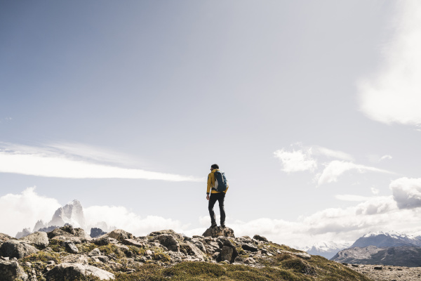 hiker with backpack standing on mountain