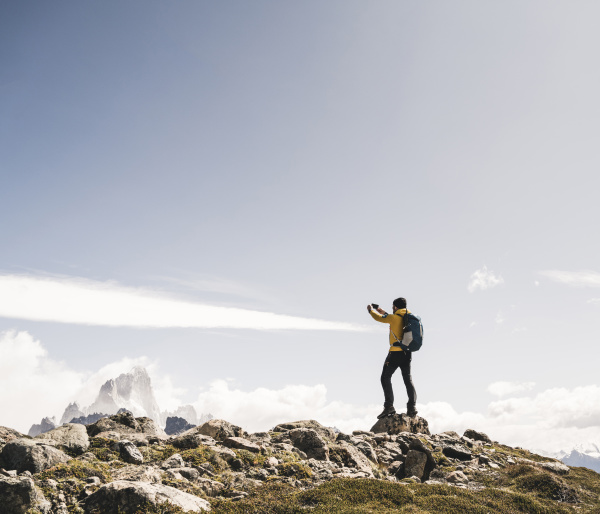 man photographing while standing on mountain