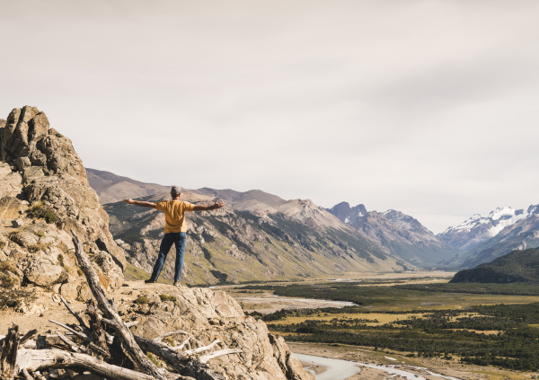 male hiker with arms outstretched looking