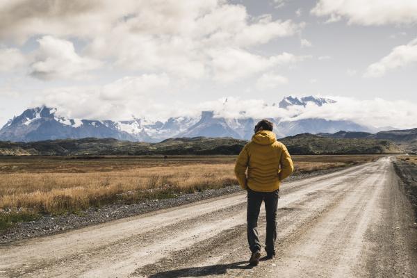 mature man walking on dirt road