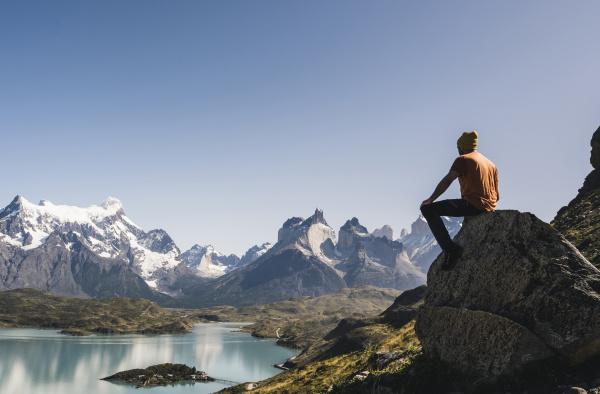 mature man sitting on rock against