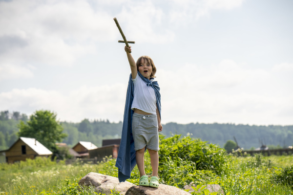 playful boy wearing cape holding toy