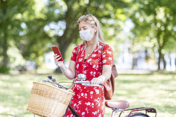 woman with bicycle wearing mask while